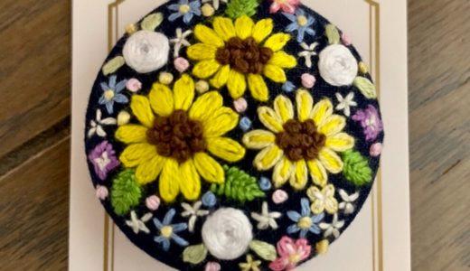 円の中に咲く小さな世界・ひまわりと白バラのブローチ